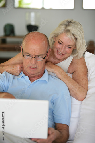 Senior couple sat on the sofa surfing the internet
