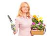 A female gardener holding flowers and gardening equipment