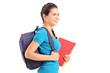 A female student with backpack walking and holding book