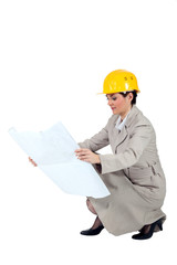 Female entrepreneur crouching on white background