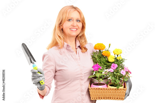 A female gardener holding flowers and gardening equipment