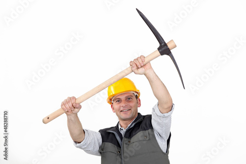 Construction worker carrying a pickaxe