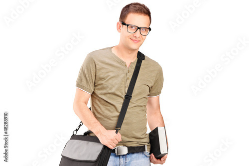 A male student with shoulder bag holding a book