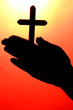 man hands with crucifix, on red background.