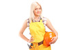 A smiling female worker with a tool belt holding helmet
