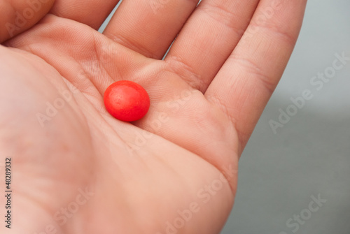 red dragee in doctor hand, macro view