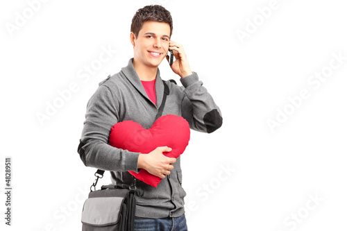 A smiling student holding a red heart and talking on a phone