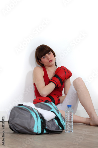 Female boxer sitting on the floor after training