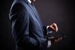 Businessman holding digital tablet on black background