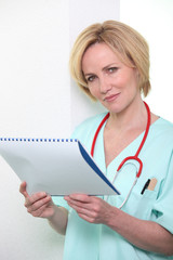 A nurse reading a file.