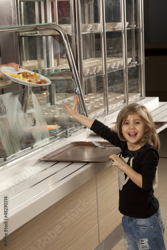 little girl in cafeteria line trying to take her healthy meal