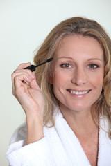 Blond woman in bathrobe holding mascara brush
