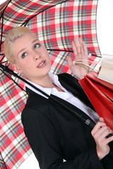 elegant woman holding shopping bags and an umbrella
