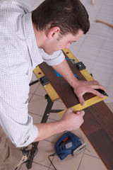 Man measuring wood flooring
