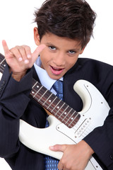 a little boy playing guitar and doing the horn sign