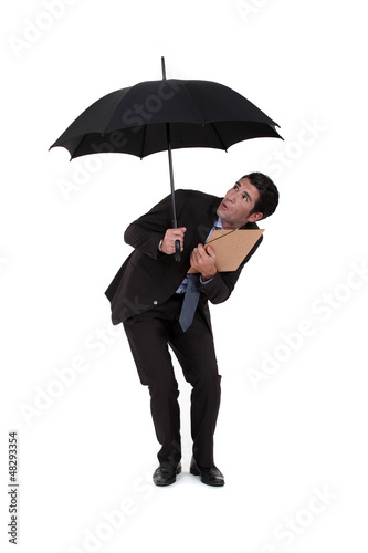 Businessman discovering a hole in his umbrella