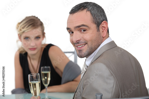 A nice couple having champagne in a restaurant.