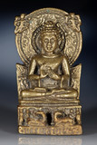 Bronze figurine of sitting Buddha on dark  blue background