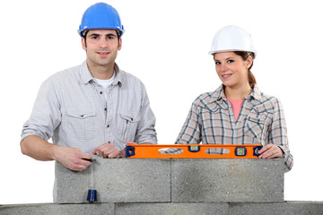 craftsman and craftswoman building a wall