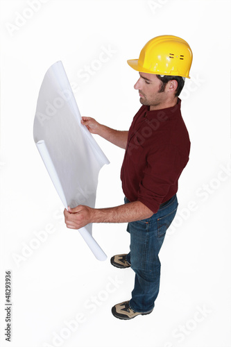builder looking at blueprints in construction site