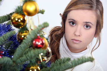 woman posing next to a Christmas tree