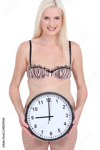 Woman in underwear holding wall clock