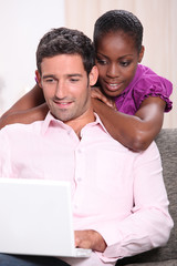 Couple looking at a laptop computer at home