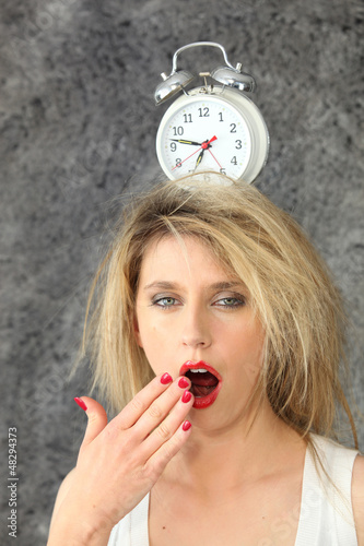 Blond woman with alarm clock on head
