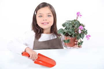 Little girl holding plant pot and trowel