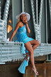 Fashion model in white hat and blue dress under the bridge
