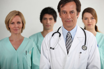 A doctor and three nurses behind him, all looking at us.