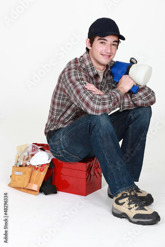 Tradesman posing for the camera with his tools