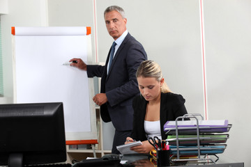Businessman stood by flip-chart