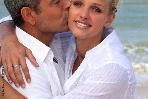 man kissing his blonde girlfriend at beach