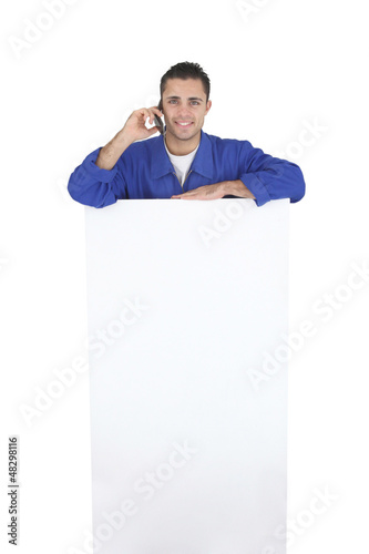 Electrician stood by blank poster surrounded by equipment