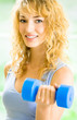 Young smiling woman with dumbbells, indoors