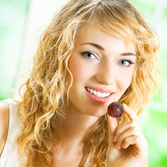 Young happy woman eating grape