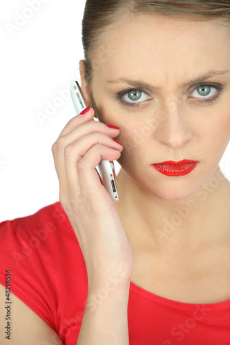 Annoyed woman in red using a cellphone