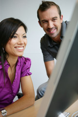 happy young woman and man working on laptop
