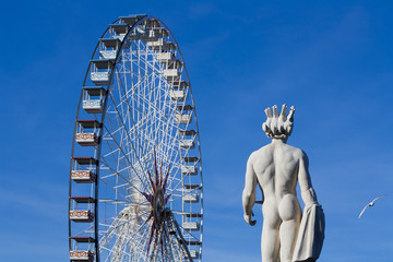 Ferris wheel in the deep blue sky with a statue beside, Nice