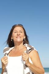 Beautiful mature woman enjoying retirement at beach