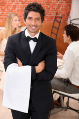 waiter facing the camera, behind a couple at restaurant