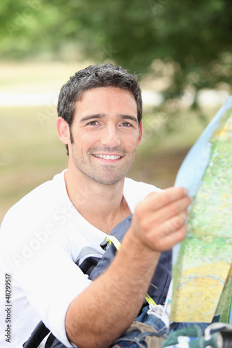 30 years old man watching a map in the forest
