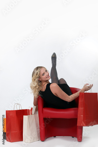 Woman sat in chair next to shopping bags
