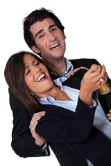 Laughing business couple celebrating with champagne