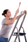 Woman with paint brush climbing step ladder