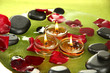 spa stones with rose petals and candles in water on plate