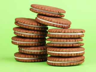 Chocolate cookies with creamy layer on green background