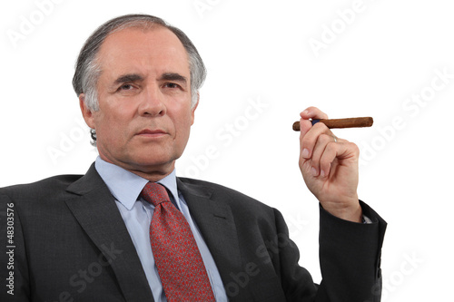 A mature businessman smoking a cigar.