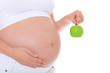 Schwangere Frau hält grünen Apfel